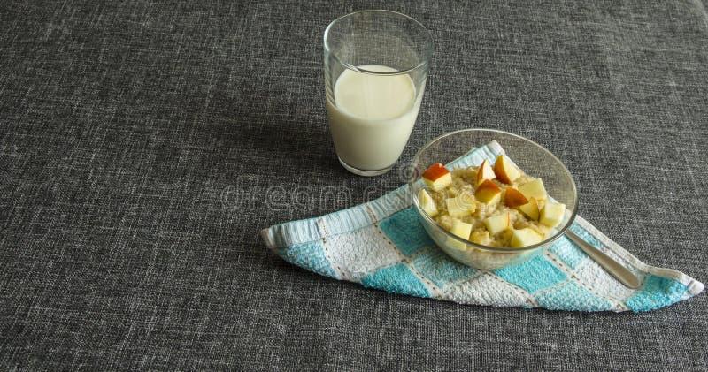 Owsianka z jabłko plasterkami, szkło mleko fotografia stock