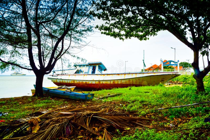 Oxidado abandonou o barco de pesca velho deixado na praia imagem de stock