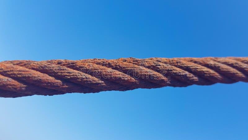 oxiderade gripa in i varandra trådöglaskablar i förgrunden med himmel- och havsbottnar Bild som tas i Lanzarote, Spanien arkivfoto