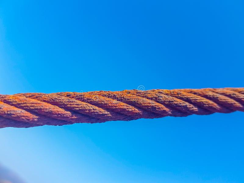 Oxidized interlocked wire loop cables in the foreground with sky and sea bottoms. Image taken in Lanzarote, Spain. Steel hook metal iron industry industrial royalty free stock images