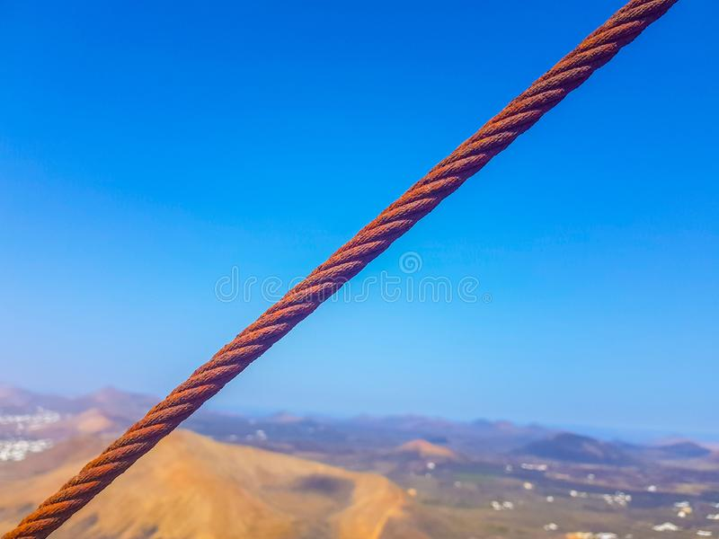 Oxidized interlocked wire loop cables in the foreground with sky and sea bottoms. Image taken in Lanzarote, Spain. Steel hook metal iron industry industrial royalty free stock image