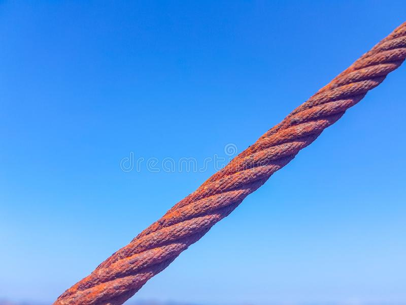 Oxidized interlocked wire loop cables in the foreground with sky and sea bottoms. Image taken in Lanzarote, Spain. Steel hook metal iron industry industrial royalty free stock photos