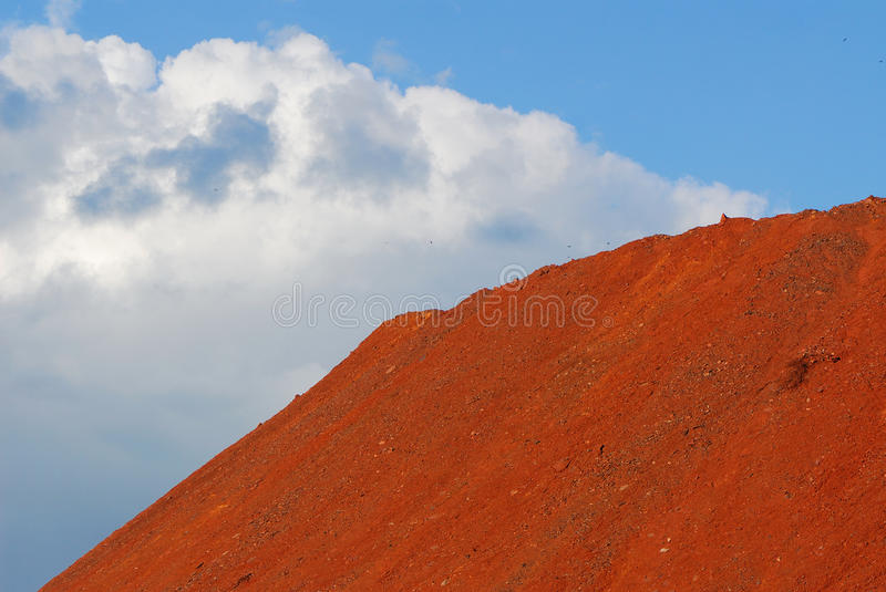 Oxidized iron. Storehouse, red color of oxidized iron ores on background of sky with clouds royalty free stock images