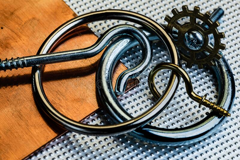 An oxidized and used copper and Stainless steel surface with several stainless steel rings and screw hooks, a brass screw hook. And a brass gear.  Industrial stock photography