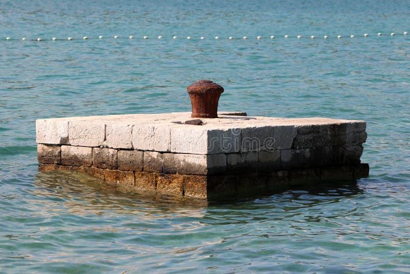 Oxidou completamente o poste de amarração dilapidado da amarração do ferro no meio do cais de pedra cercado com o mar calmo usado fotos de stock