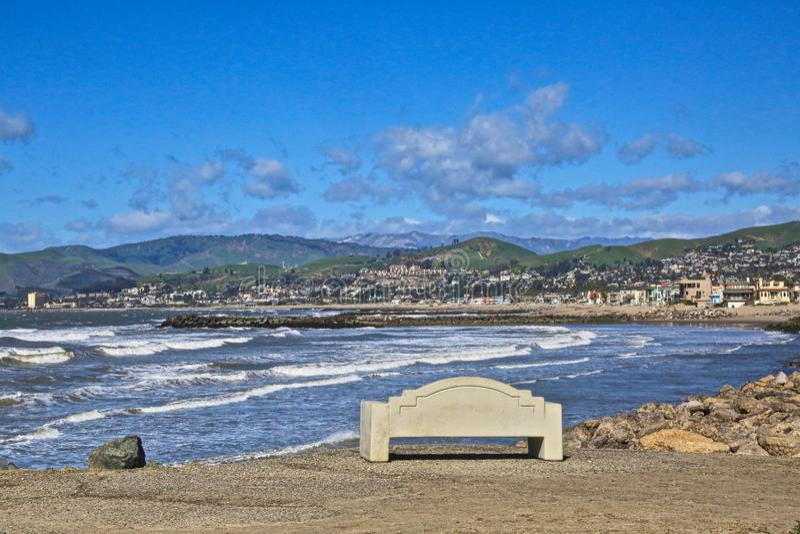 Oxnard California coastline. Beautiful sunny day Pacific coastline in Oxnard California with bench Ocean waves buildings mountains and blue skies stock images