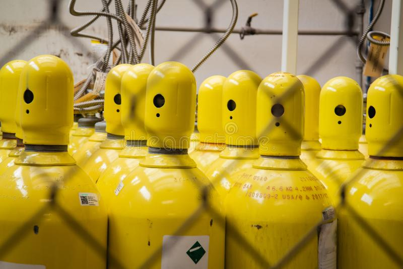 Oxygen cylinder container yellow tubes. Yellow oxygen cylinders containers behind a steel net hydrogen container hydrogen royalty free stock photo