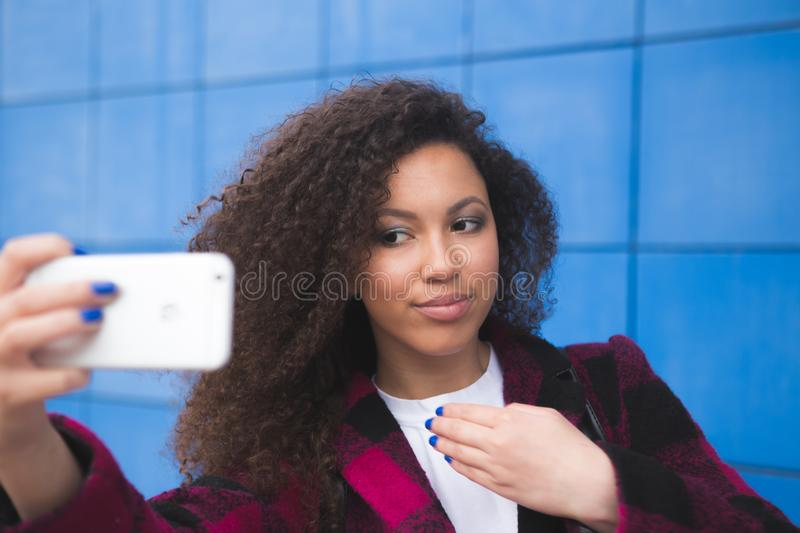 Smiling happy young African American girl taking selfie on smartphone on blue background. Technological concept royalty free stock photo