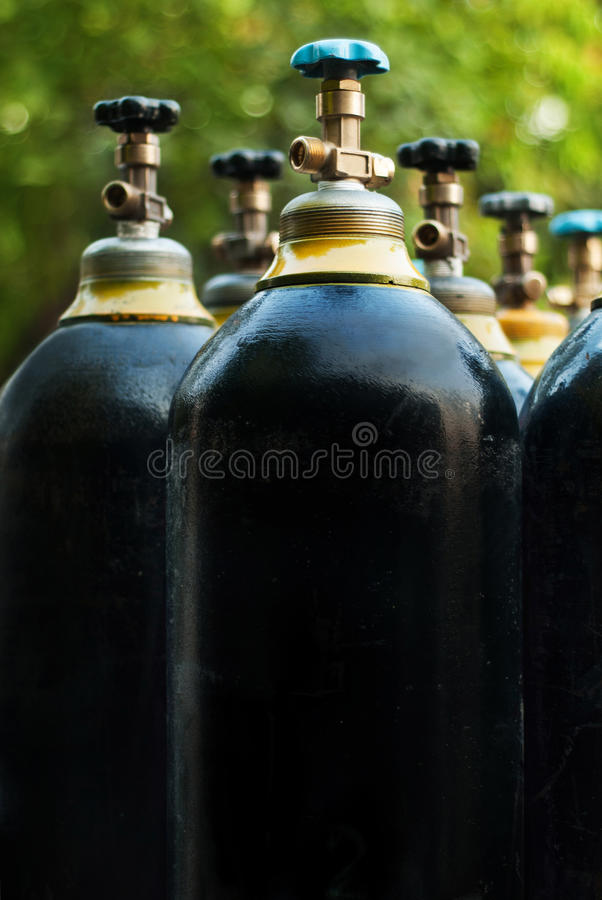 Oxygen tanks. On the background of yellow-green leaves stock images