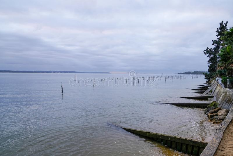 Oyster farm in Cap Ferret with Arcachon Dune du Pilat view in sunrise winter day. An Oyster farm in Cap Ferret with Arcachon Dune du Pilat view in sunrise winter royalty free stock photo