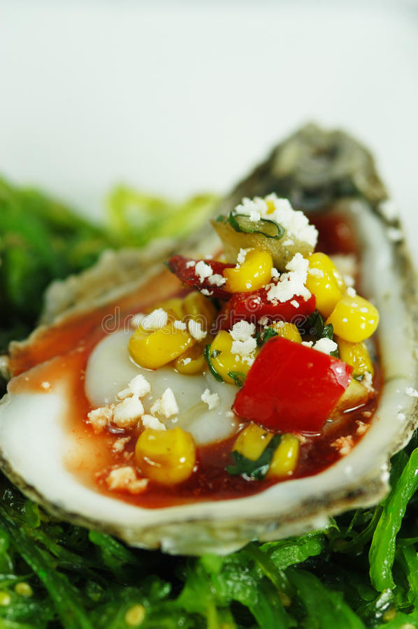 Oyster on the Half Shell with Relish. Oyster on the half shell with corn and pepper relish royalty free stock photos