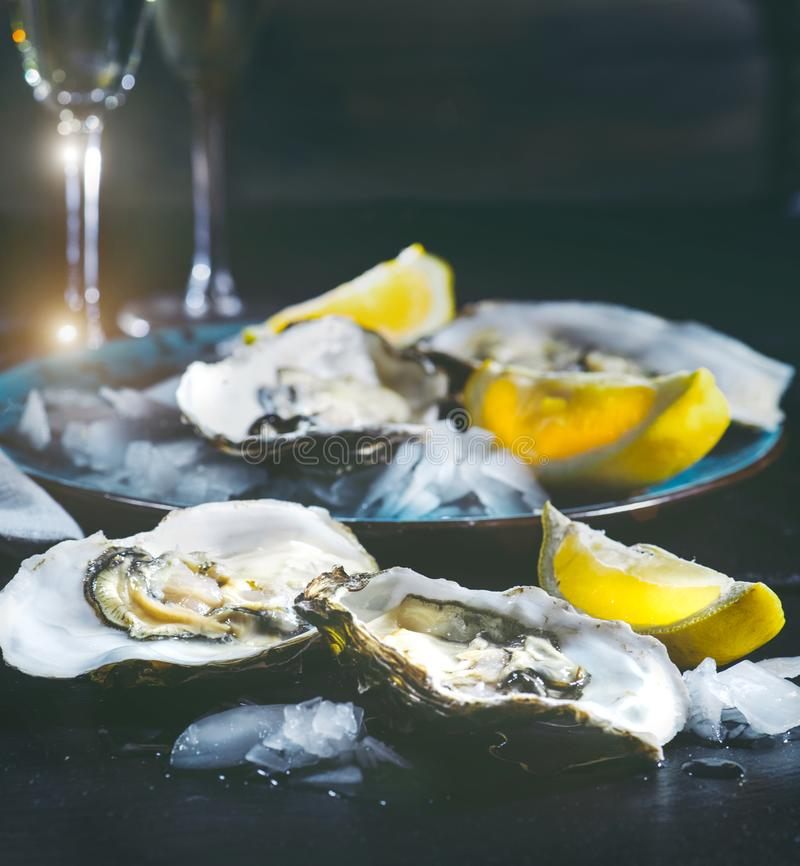 Oysters closeup on blue plate. Served table with fresh oysters, lemon and ice. Healthy sea food. Oyster dinner with champagne stock photo
