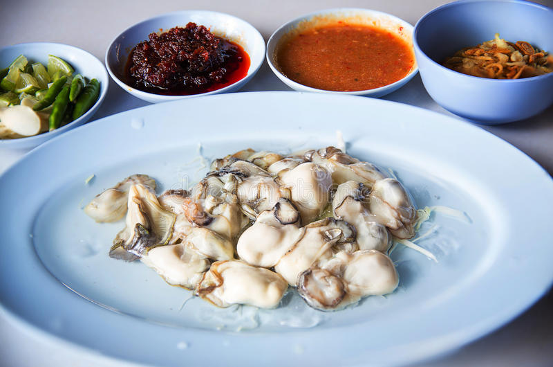 Oysters food and chili sauce,Thai food is Oysters with Herbs or Oyster Spicy Salad. Oysters with chili paste, fried onions,red onion fried Thai cuisine style stock photography