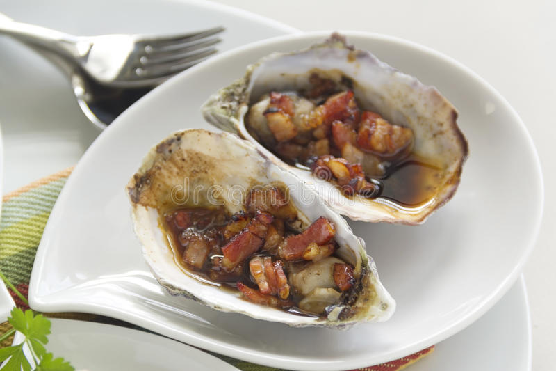 Oysters Kilpatrick. Delicious oysters kilpatrick with bacon and worcestershire sauce ready to serve royalty free stock image