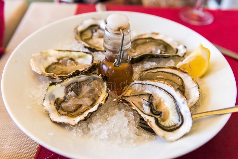 Oysters with lemon on a plate, Sete, France. Close-up. Oysters with lemon on a plate, Sete, France. Close-up stock photography