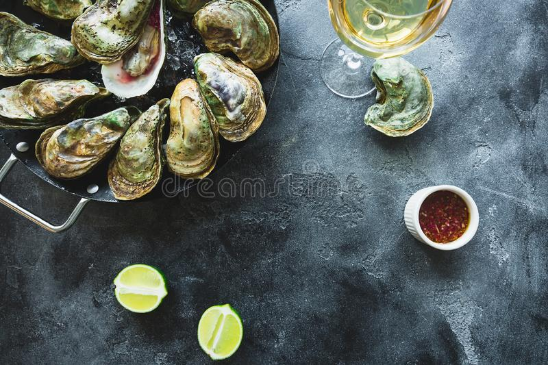 Oysters platter with white wine and lime on dark background. Flat lay. Top view stock photo