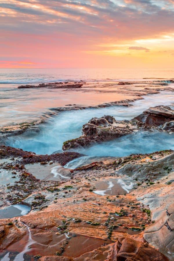 Ozean, der in die Küstenkanäle abgefressen in Felsen und in einen erstaunlichen Sonnenaufgang fließt lizenzfreie stockfotografie