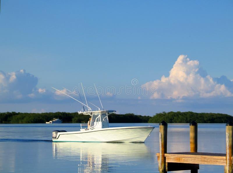 Ozean-Fischerboot heraus auf der Bucht, die Dock mit Reflexion O sich nähert lizenzfreie stockfotografie