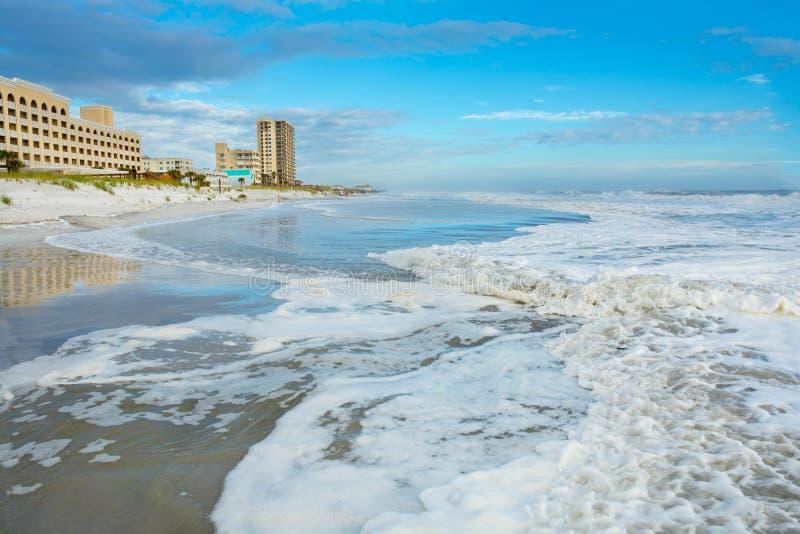 Ozean- und Strandlandschaft, bewölkter blauer Himmel und Hotels und Gebäude im Hintergrund stockbild