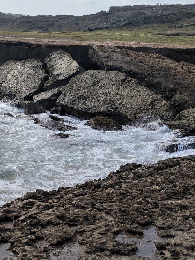 Ozean-Wasser in den Schatten gestellt durch Flusssteine stockfoto