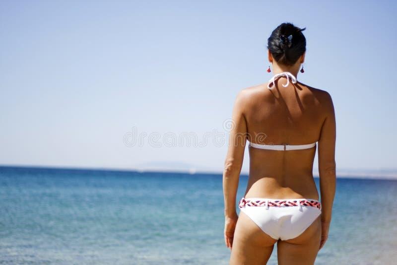 Ozeanferienrückzugfrau, die am Strand sich entspannt stockbild