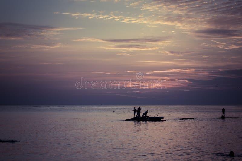 Ozeanlandschaft bei Sonnenuntergang Schattenbilder von Fischern lizenzfreie stockfotografie