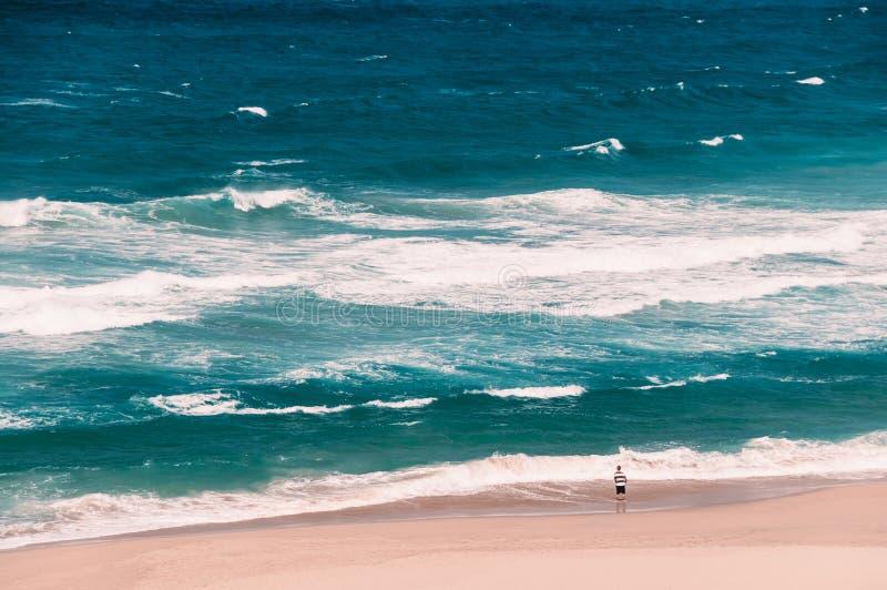 Ozeanstrand mit großen Wellen, ein Fischer, der mit einem Fischen steht lizenzfreie stockfotos