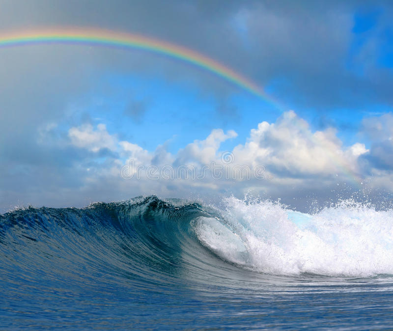 Ozeanwelle im tropischen Paradies und im Regenbogen stockbilder