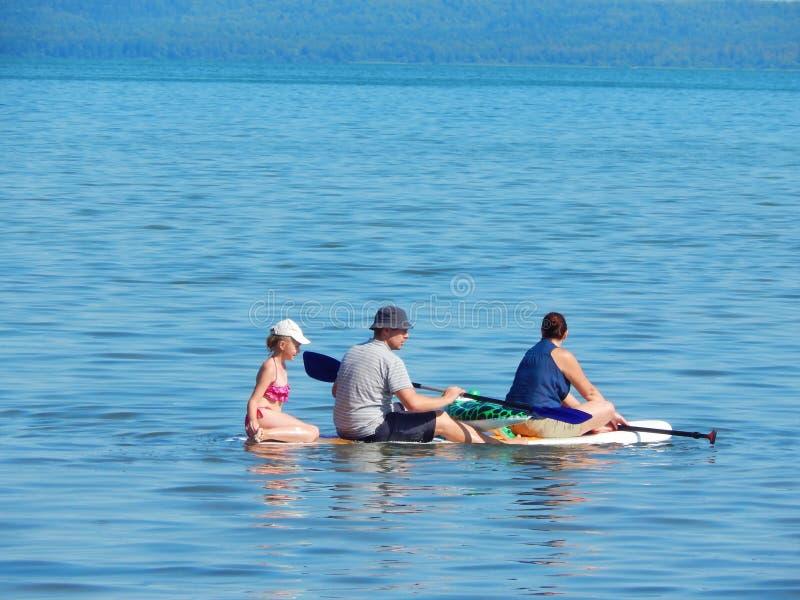 Pá de pé que surfa Uma família está montando uma placa fotografia de stock