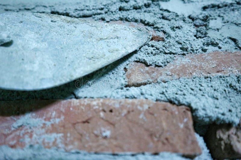 Pá de pedreiro e parede de tijolo com cimento do almofariz imagem de stock