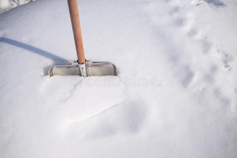 Pá do metal com um punho de madeira, estando em um monte de neve, na imagens de stock royalty free
