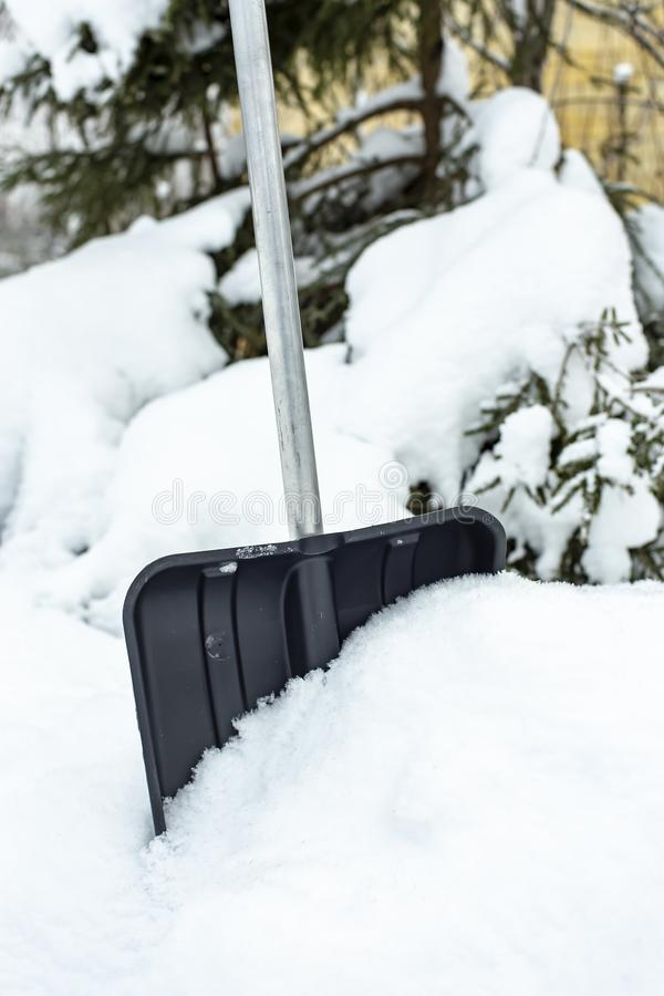 Pá plástica preta com um punho de alumínio, estando em um monte de neve e pronto para trabalhar, contra o contexto de um coberto  fotos de stock