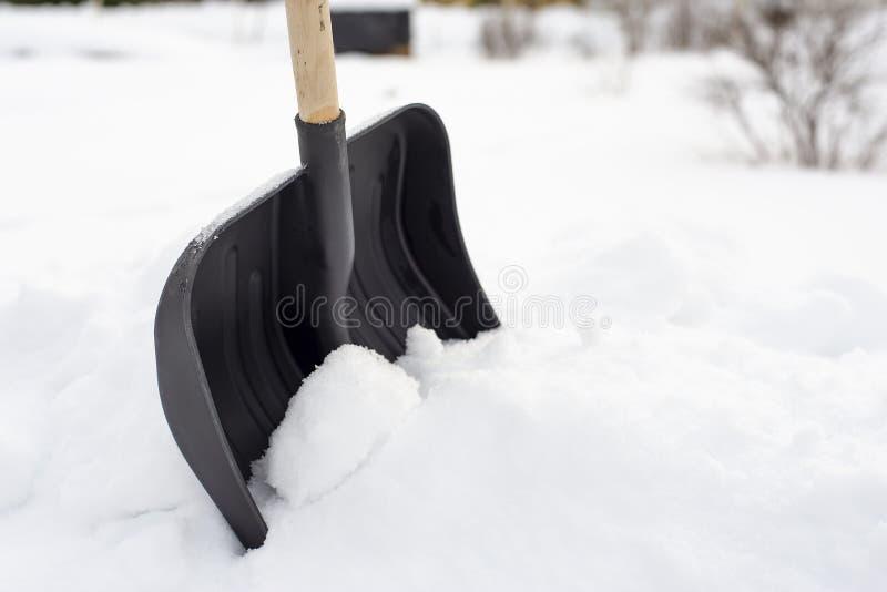 Pá plástica preta com um punho de madeira que está em um snowdrif foto de stock