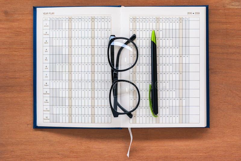 Página aberta do calendário do livro do planejador do diário com vidros e pena fotografia de stock