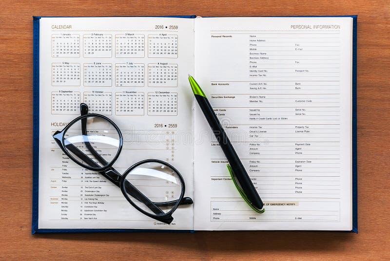 Página aberta do calendário do livro do planejador do diário com vidros e pena no th fotografia de stock royalty free