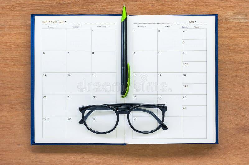 Página abierta del calendario del libro del planificador del diario con los vidrios y pluma en el th fotos de archivo