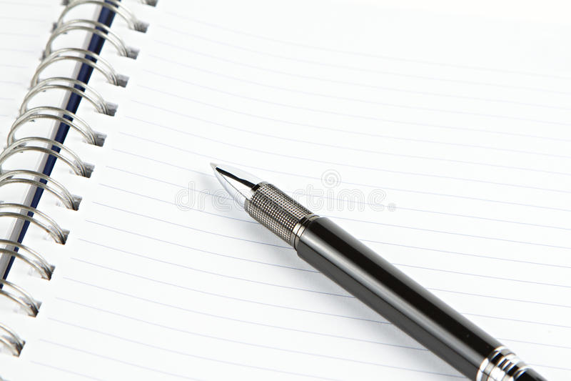 Página do caderno com pena preta imagem de stock