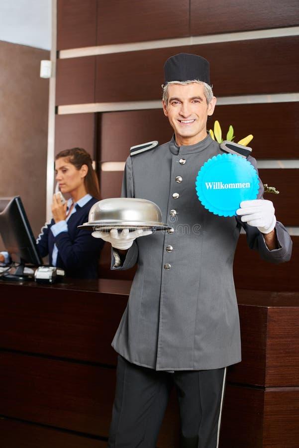Página do hotel que guarda o sinal de Willkommen imagem de stock