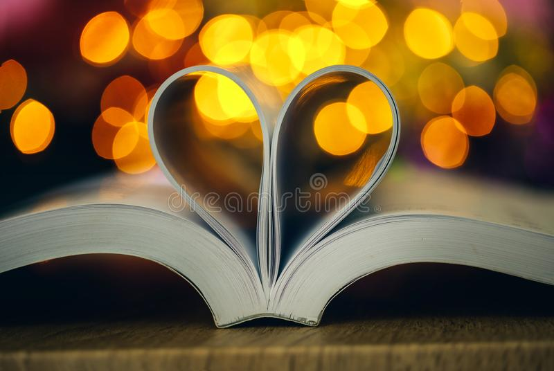 A página do livro decora à forma do coração com lig do bokeh da celebração foto de stock royalty free