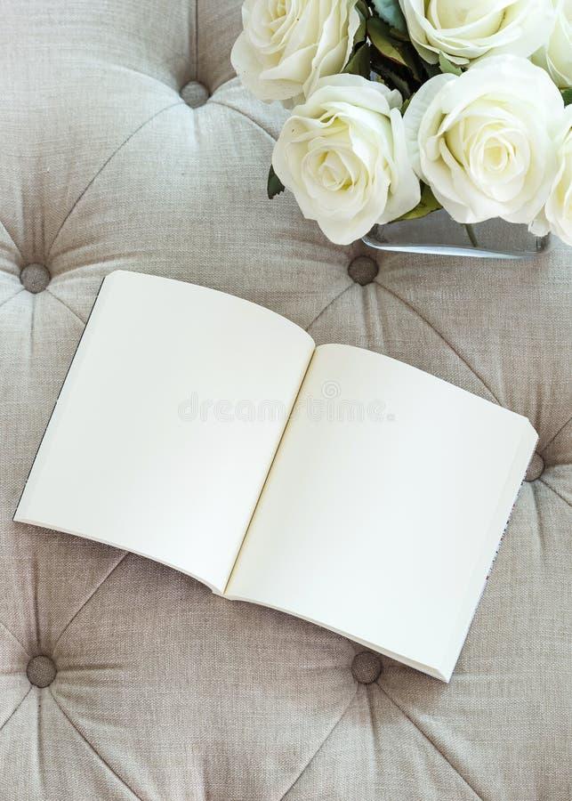 Página en blanco abierta del libro en el sofá con la flor de la rosa del blanco foto de archivo