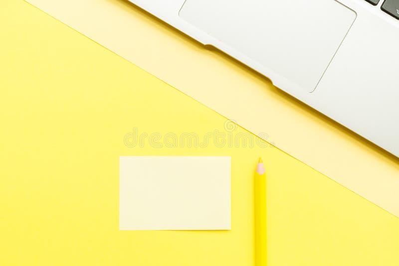P?gina en blanco de la maqueta con el ordenador port?til y el l?piz en fondo amarillo Visi?n superior con el espacio de la copia  fotografía de archivo libre de regalías