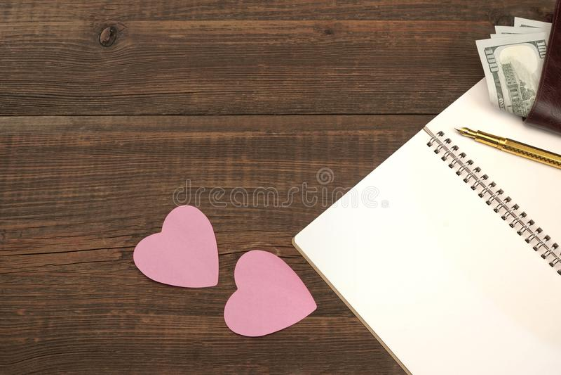 Página espiral vazia do bloco de notas, corações, carteira na tabela de madeira Backgro foto de stock royalty free