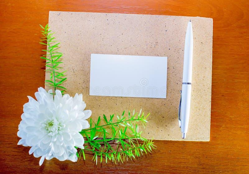 Página, pluma y flor de la cartulina fotografía de archivo