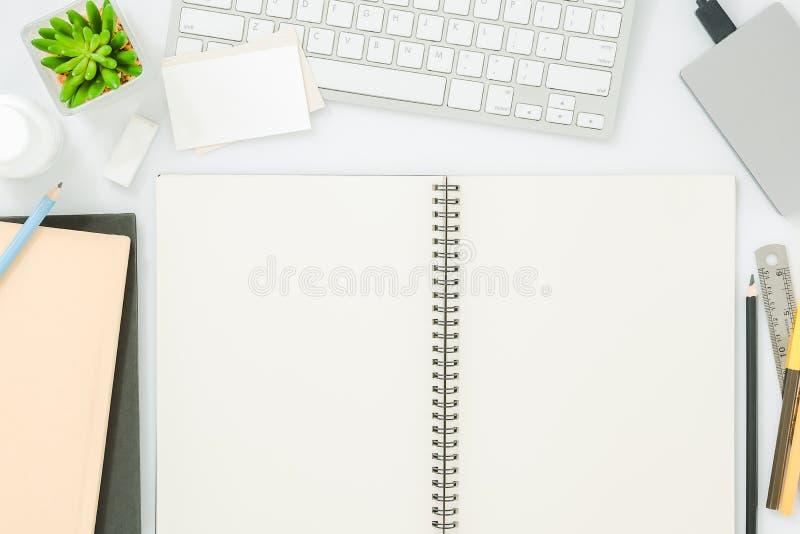 Página vazia do caderno na tabela branca moderna da mesa de escritório com fontes para o modelo Vista superior, configuração lisa foto de stock