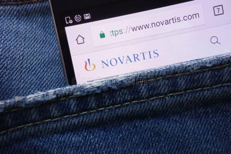 Página web de Novartis exhibida en el smartphone ocultado en bolsillo de los vaqueros fotografía de archivo