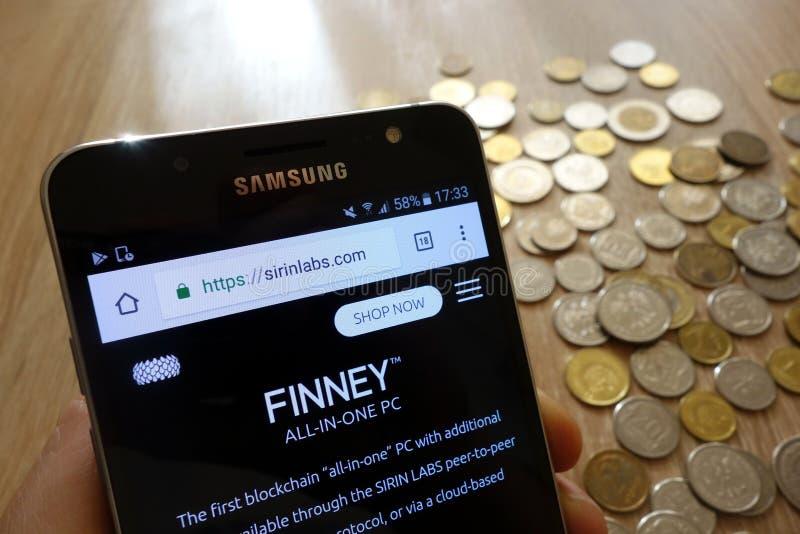 Página web simbólica del intercambio del cryptocurrency de los laboratorios de Sirin exhibida en smartphone y la pila de monedas imagen de archivo libre de regalías