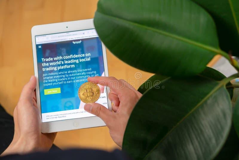 Página web y hombre de EToro con el bitcoin foto de archivo