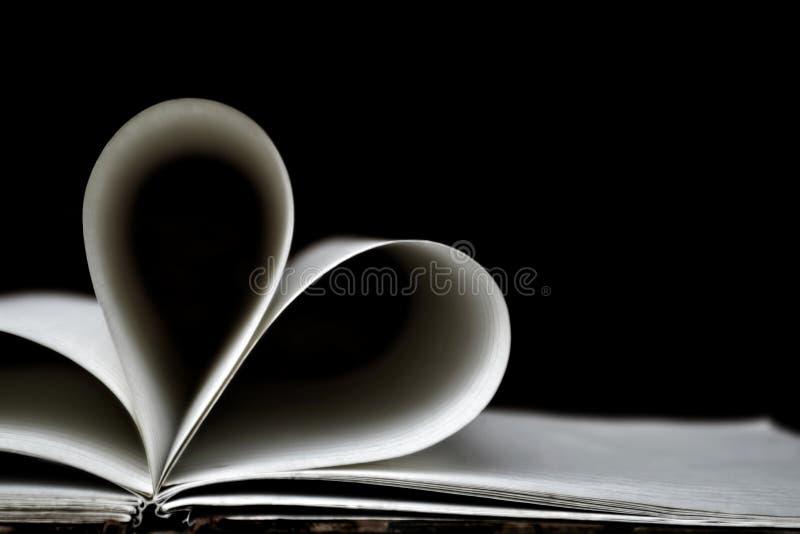 Páginas dadas forma coração do livro, fundo escuro imagens de stock royalty free