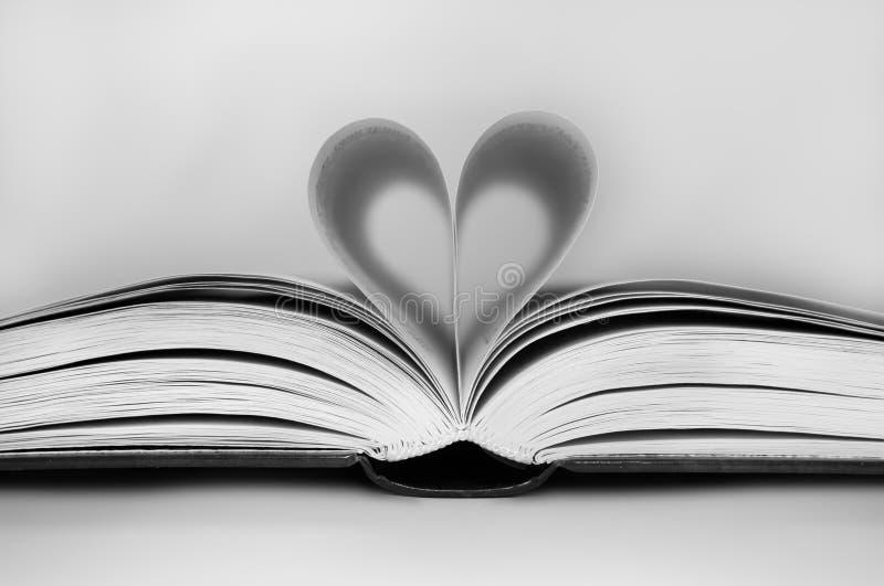Páginas de un libro doblado adentro a un corazón imágenes de archivo libres de regalías