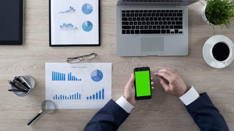Páginas del movimiento en sentido vertical del hombre de negocios en el smartphone verde en oficina, visión superior de la pantal imagenes de archivo